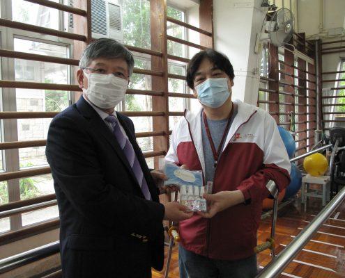 瑞林國際合作有限公司行政總裁張憲林先生(左)送贈口罩及消毒酒精噴霧予香港復康會員工。